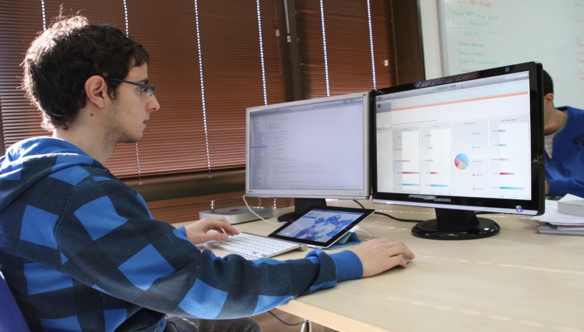 Máster Oficial en Ingeniería del Software. Imagen de un estudiante de la Escuela Técnica Superior de Ingenieros Informáticos trabajando ante dos pantallas de ordenador.